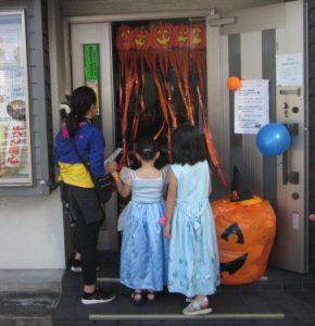 子どもが家を訪問しているハロウィンの写真